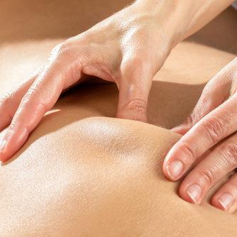 Detail of hands massaging shoulder blade.